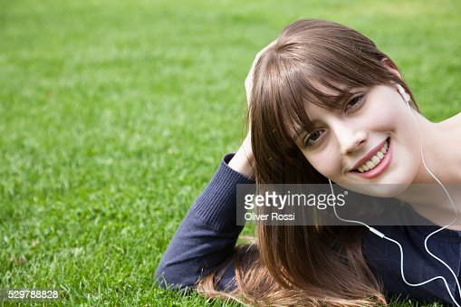 Young woman listening to earbuds : Stock-Foto