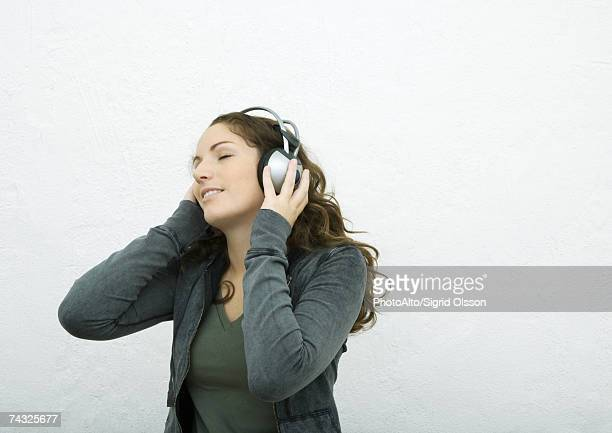 Young woman listening to headphones, eyes closed, white background