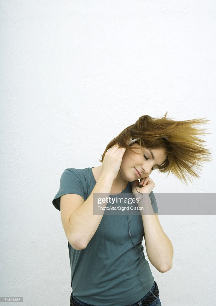 Young woman listening to headphones with eyes closed, swinging hair : Stock Photo