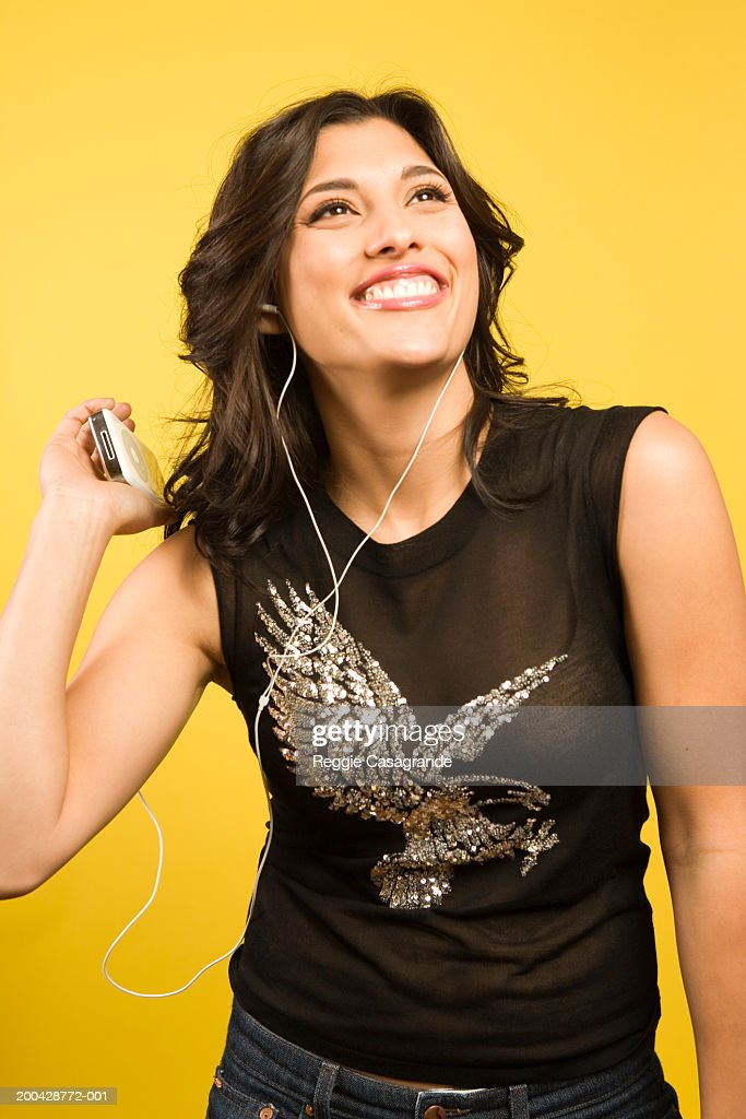 Young woman listening to MP3 player, smiling, looking up : Stock Photo