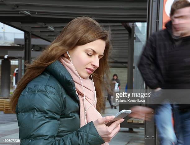 Young woman listening to music at a bus terminal