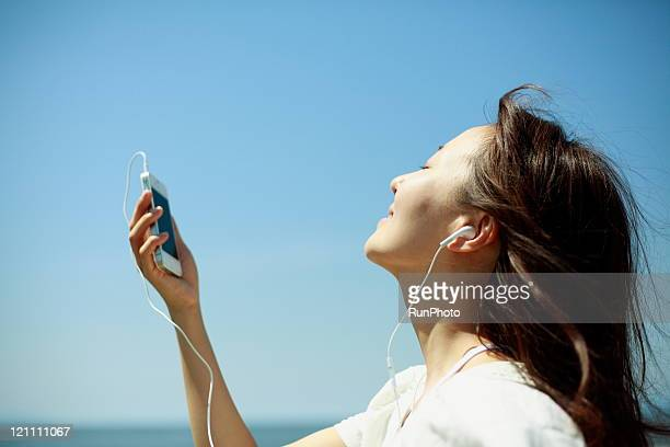 young woman listening to music at the sea
