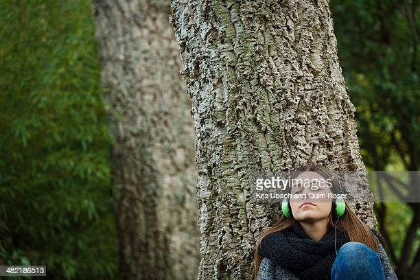 Young woman listening to music in forest