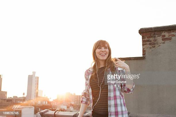 Young woman listening to music on city rooftop