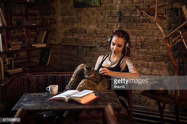Young woman listening to music on headphones in a cafe.