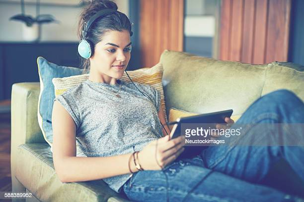 Young woman listening to music on tablet computer at home