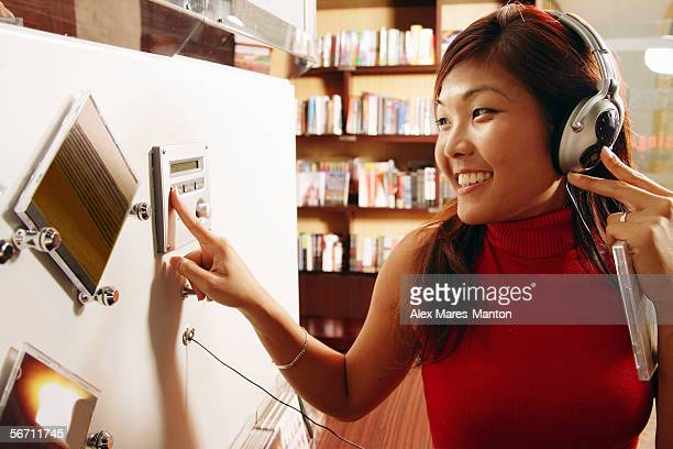 Young woman listening to music, smiling, pressing button