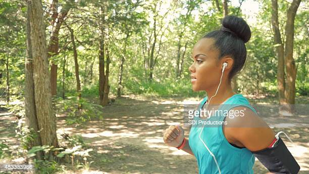 Young woman listening to music while running off road