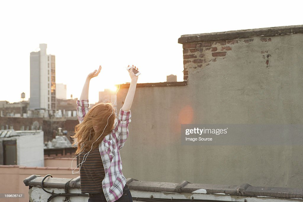 Young woman listening to music with arms raised on city rooftop : Stock Photo