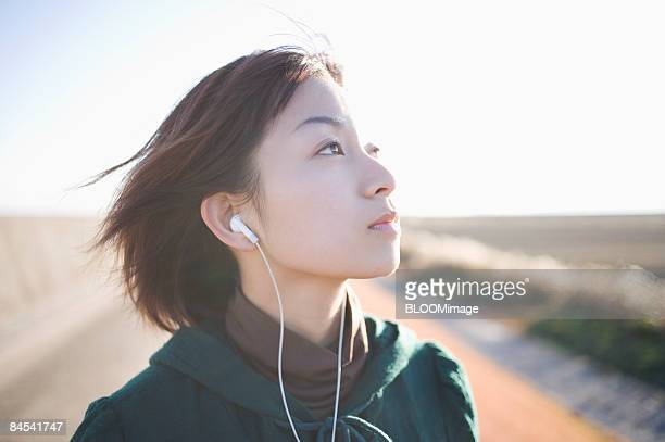 Young woman listening to music with earphones
