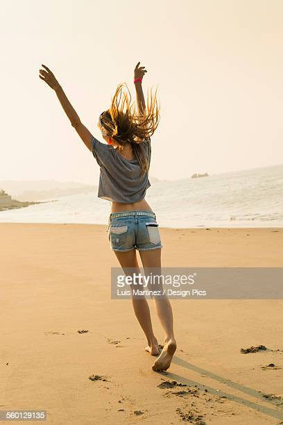 Young woman listening to music with her headphones on the beach