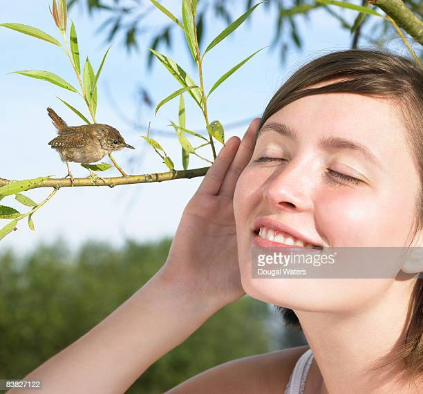 Young woman listening to small bird.