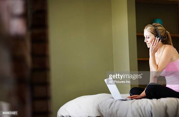 Young woman listens to music on laptop