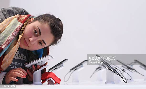 A young woman listens to sound coming from a Samsung Galaxy Note mini tablet PC at the Vodafone stand on the first day of the CeBIT 2012 technology...