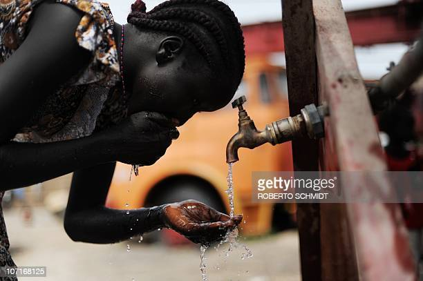 A young woman living in the village of Reer washes her face on a faucet at a newly built deep water well in the village on November 13 2010 The...