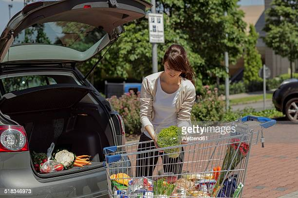 Young woman loading purchase in her car