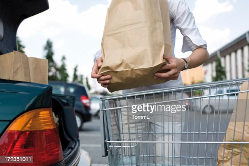 A young woman loads her groceries into her car