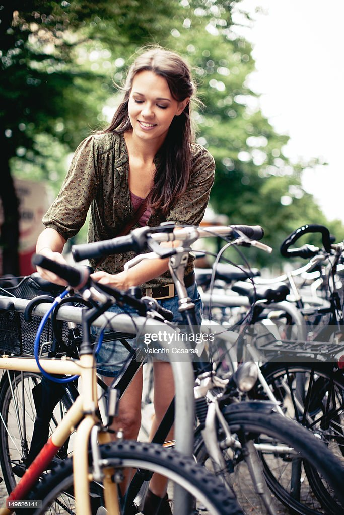 Young woman locking bicycle to bicycle rack : Stock Photo
