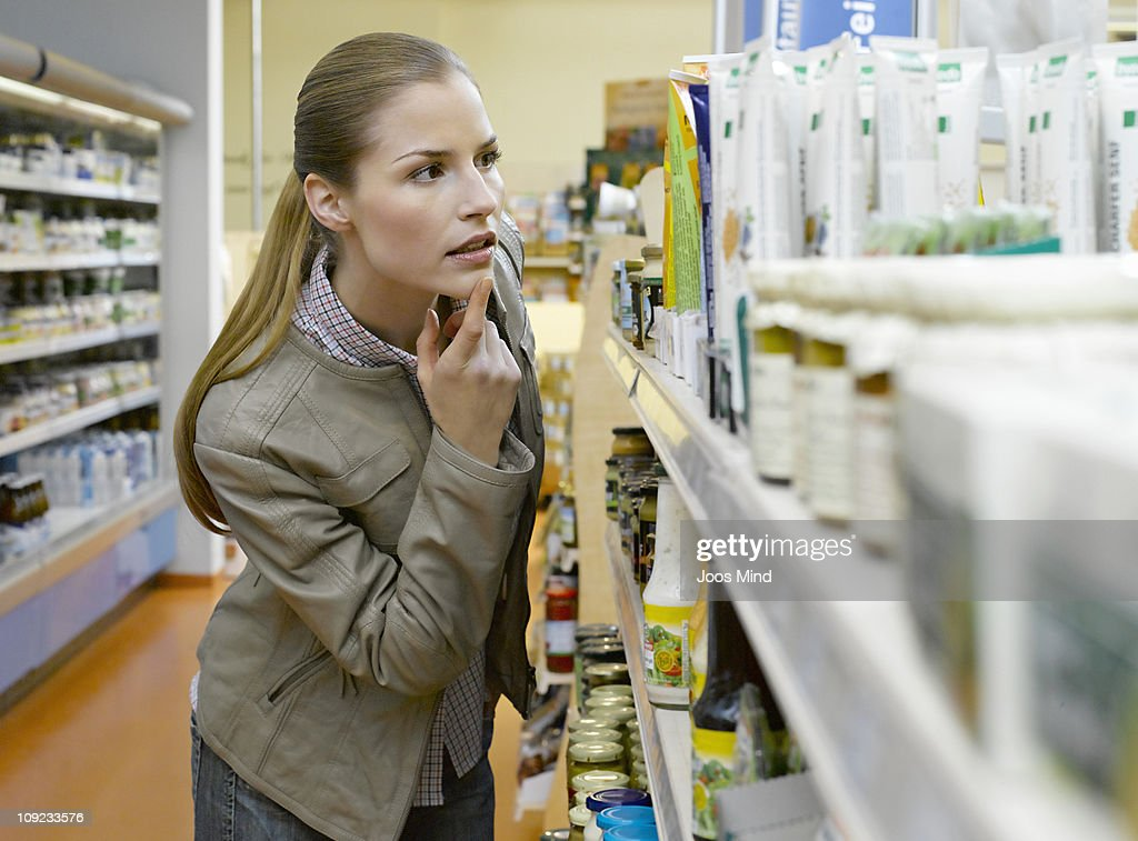 young woman loking at grocery in supermarket : Bildbanksbilder