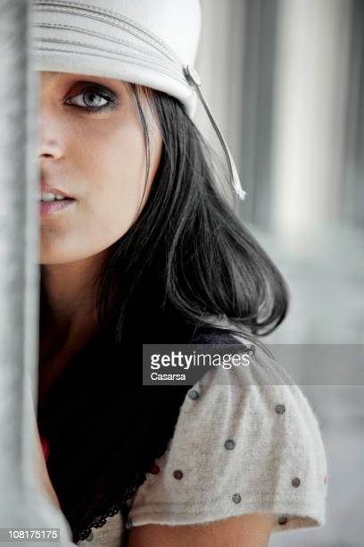 Young Woman Looking Around Corner Outside