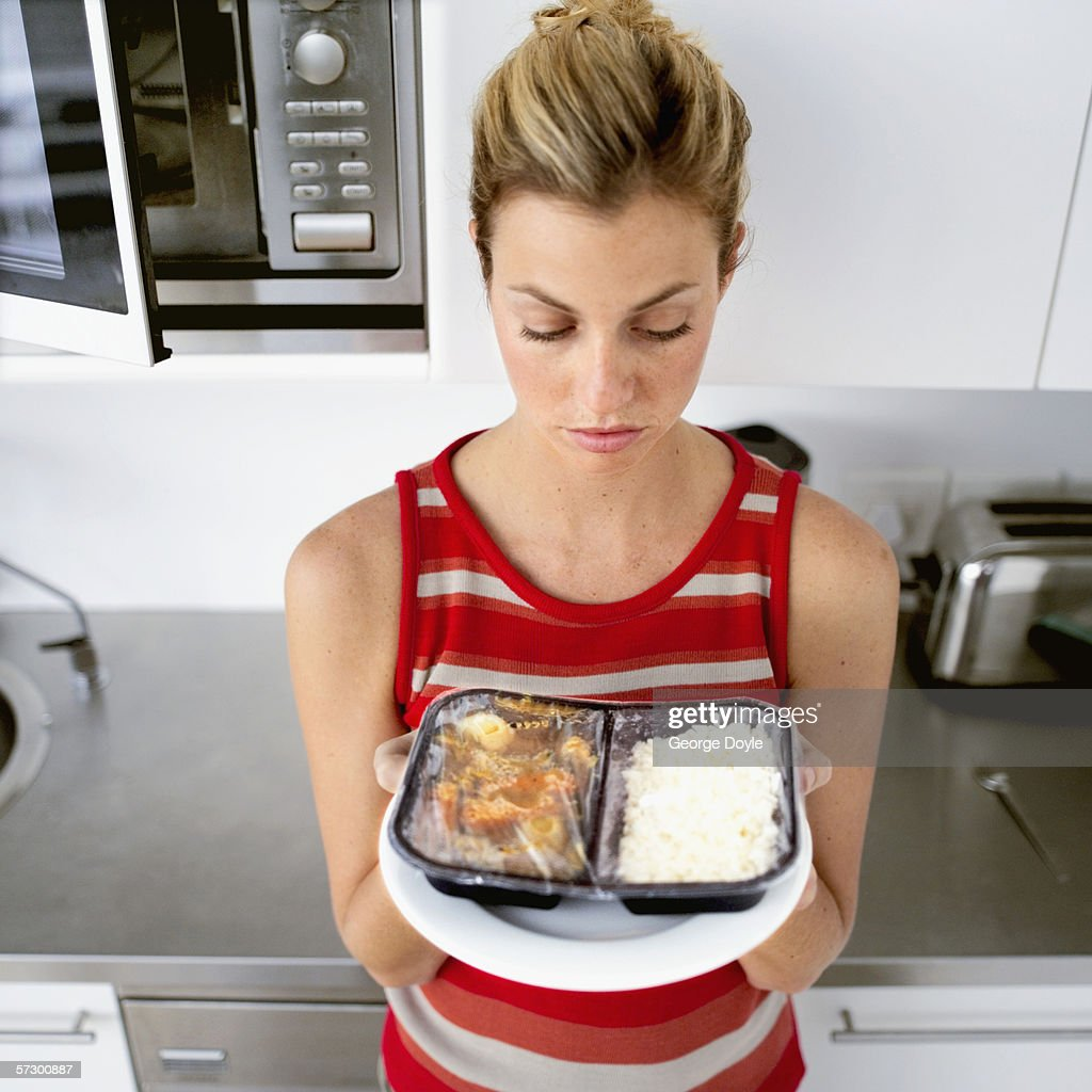 A young woman looking at a cooked microwave dinner
