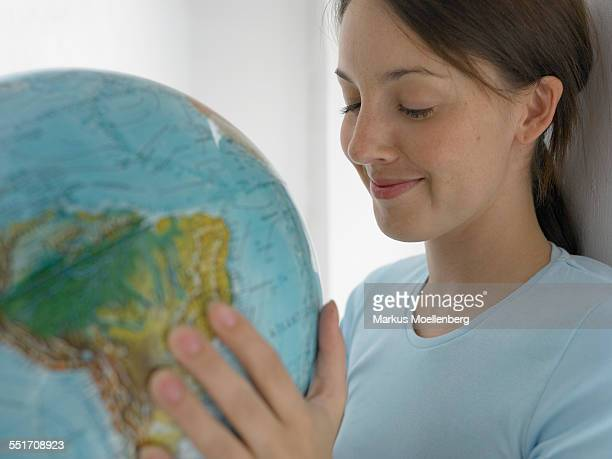 Young Woman Looking at a Globe