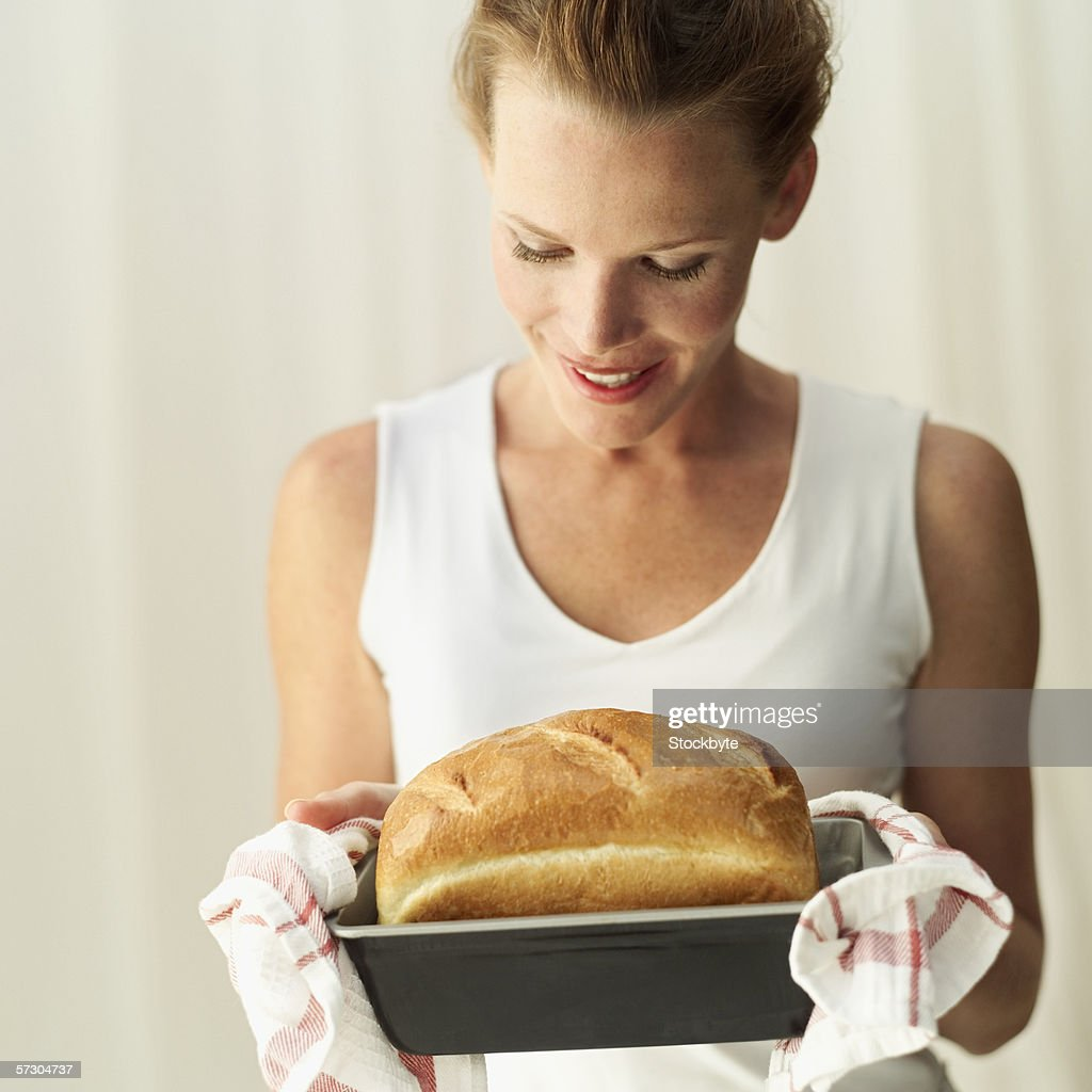 Young woman looking at a loaf of freshly baked bread : Stock Photo
