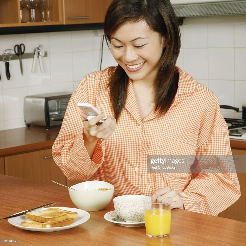 Young woman looking at a mobile phone and smiling at a kitchen counter