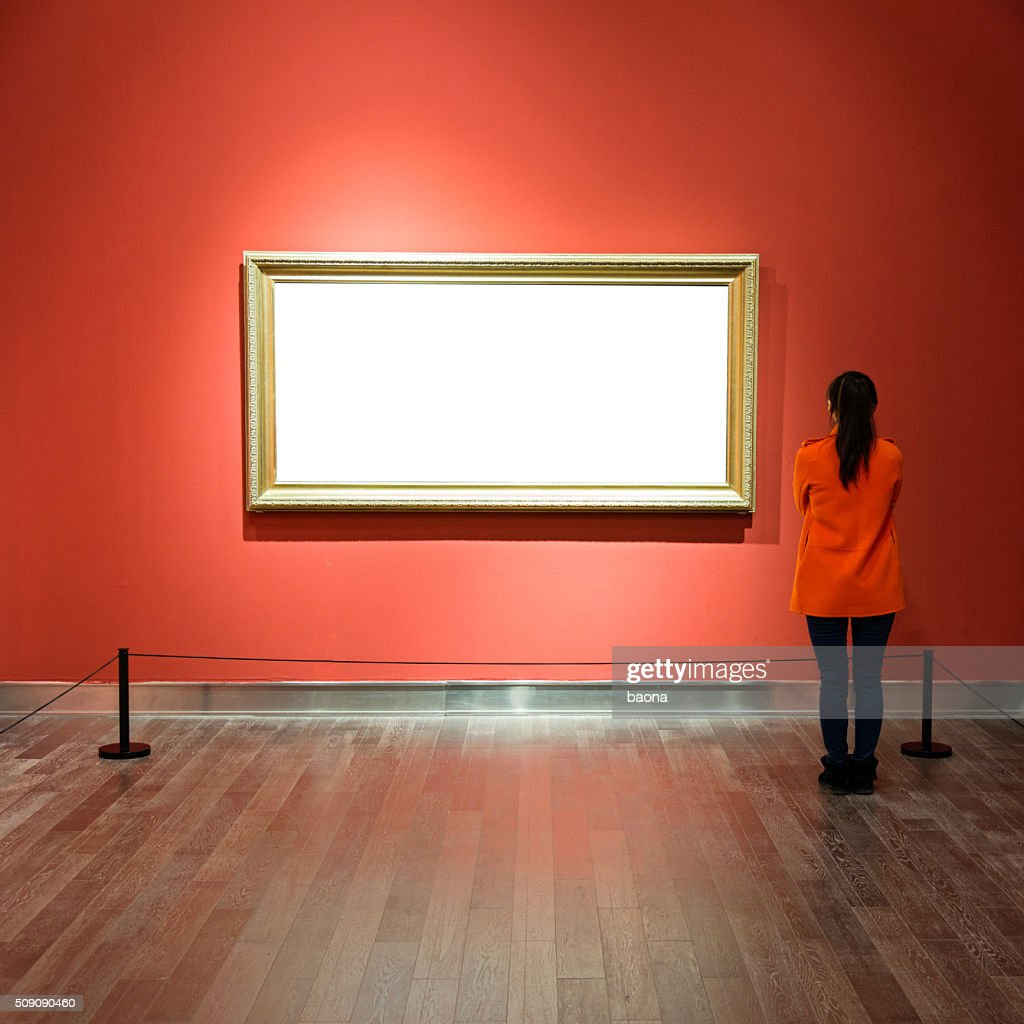Young woman looking at artwork : Stock Photo