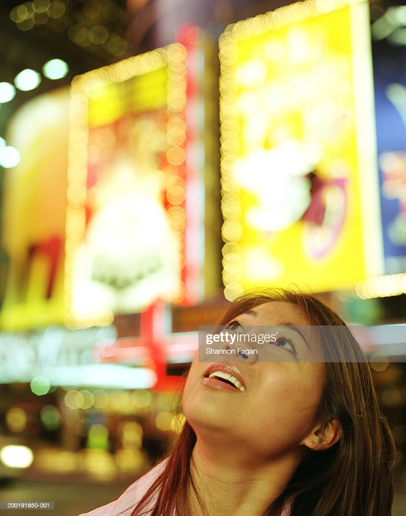 Young woman looking at billboards at night, close-up : Stock Photo