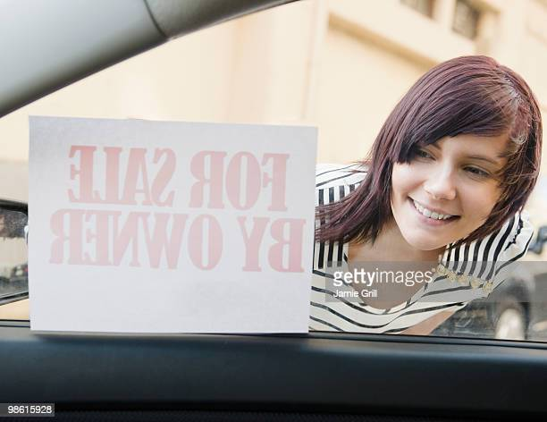 Young woman looking at car for sale