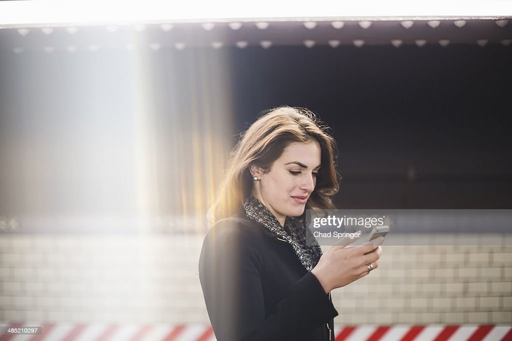 Young woman looking at cellphone in subway station
