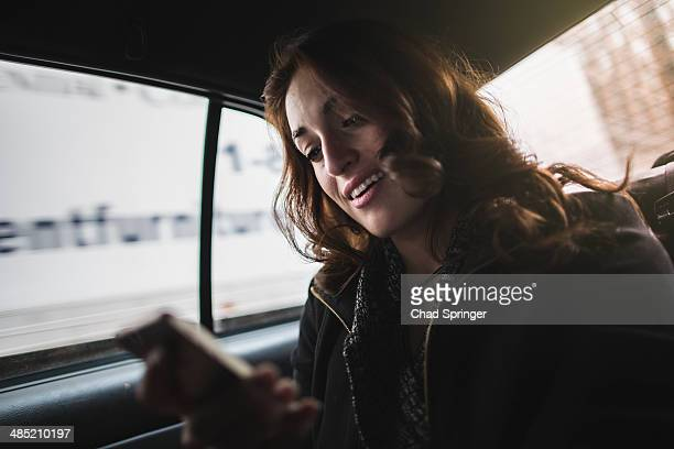 Young woman looking at cellphone in taxi