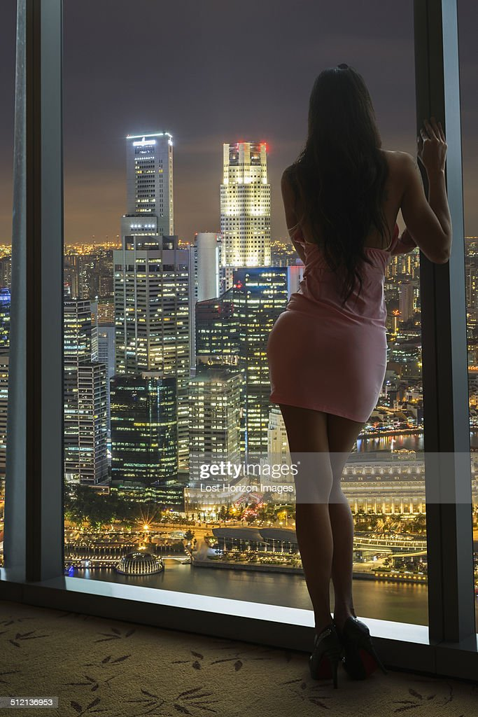 Young woman looking at city skyline from window, Singapore