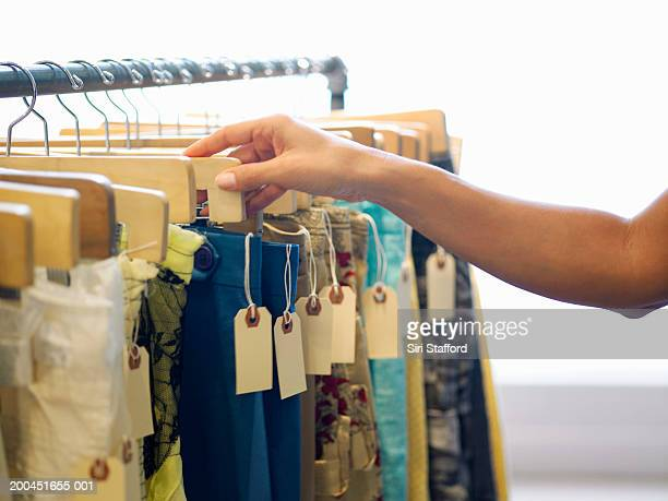 Young woman looking at clothes on rack in boutique