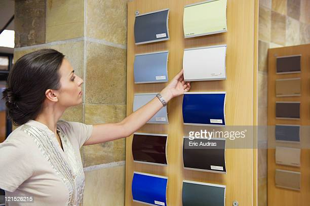 Young woman looking at color samples at car showroom