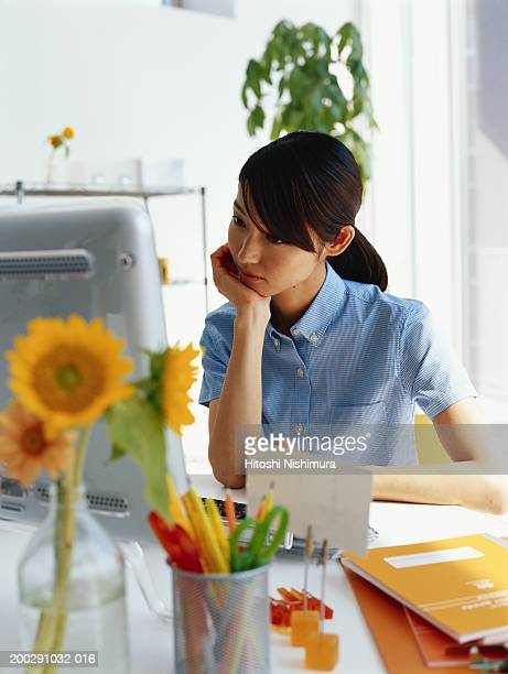 Young woman looking at computer screen, hand on chin