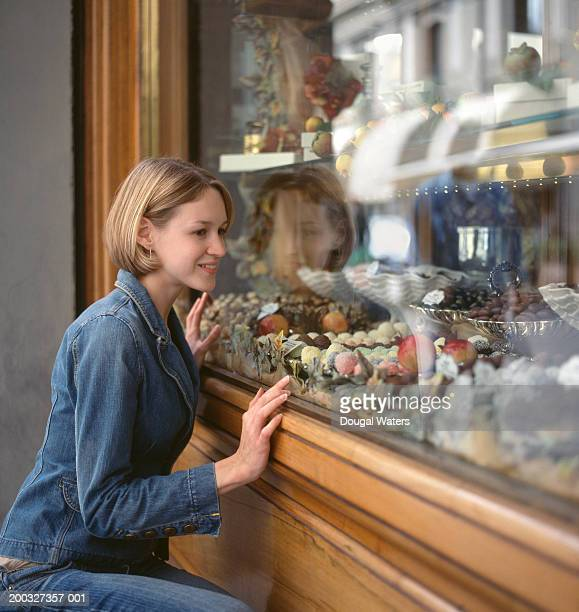 Young woman looking at confectionery display through shop window