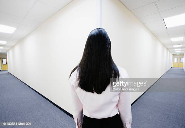 Young woman looking at corner in hallway, rear view