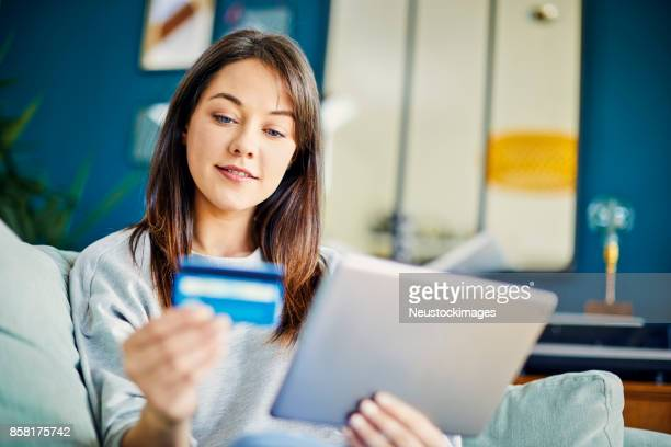 Young woman looking at credit card while using digital tablet