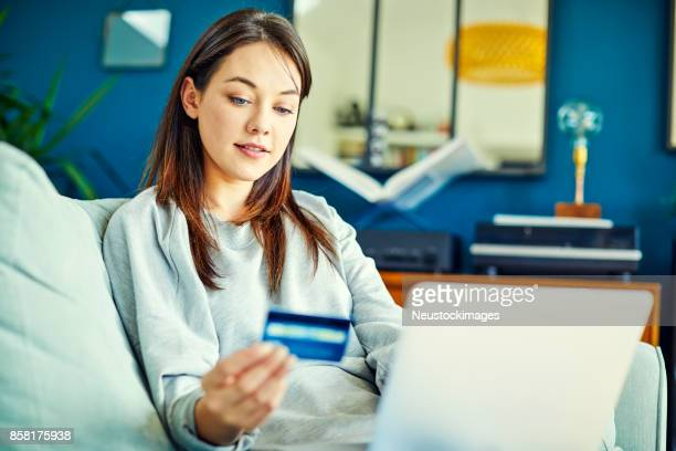 Young woman looking at credit card while using laptop
