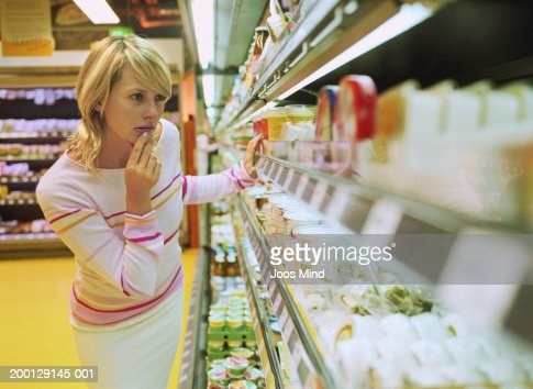 Young woman looking at dairy produce in supermarket : Foto de stock