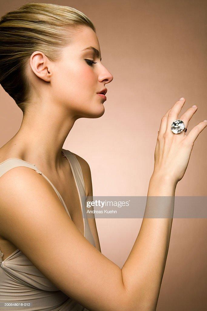 Young woman looking at diamond ring, close-up : Stock Photo