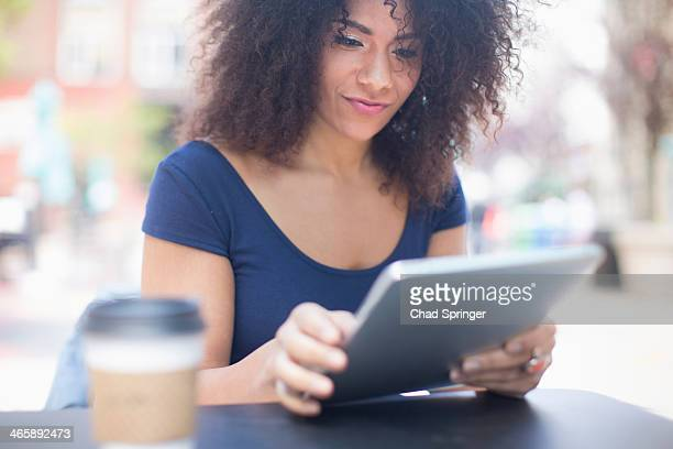 Young woman looking at digital tablet at sidewalk cafe