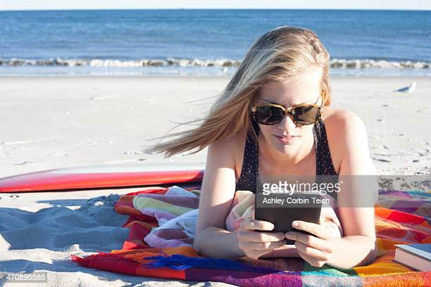 Young woman looking at digital tablet on beach, Breezy Point, Queens, New York, USA
