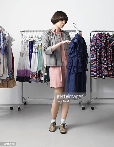 young woman looking at dress in clothing store