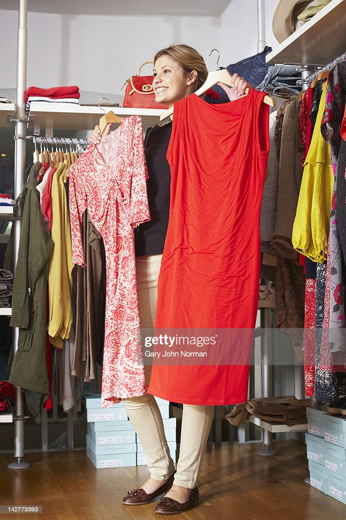 Young woman looking at dresses in boutique : Stock Photo