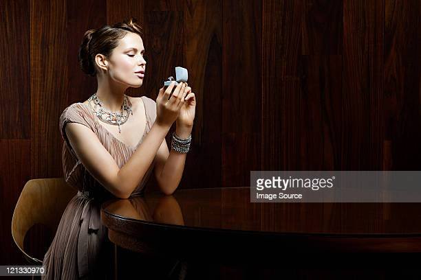 Young woman looking at engagement ring in box