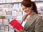 Young woman looking at greeting card from rack, side view
