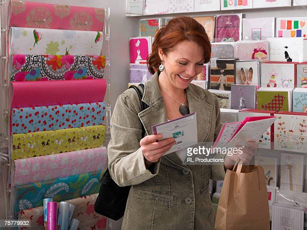 Young woman looking at greeting cards from rack, smiling